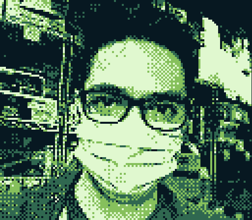 Monochrome green photo of Michael wearing a medical mask
