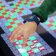 a hand touches a giant touch screen containing the videogame chogue