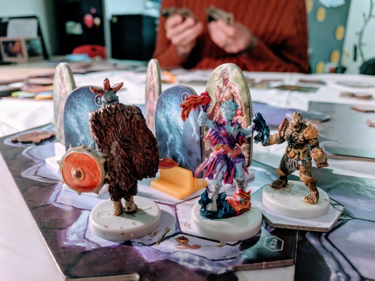 a photograph of a gloomhaven game in action, featuring several painted miniatures on a cardboard game board