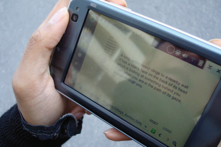 a photograph of the storytrek app, operating on a phone and held in someone's hand outdoors