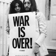 Yoko Ono and John Lennon hold a large white sign that reads War Is Over! in bold lettering