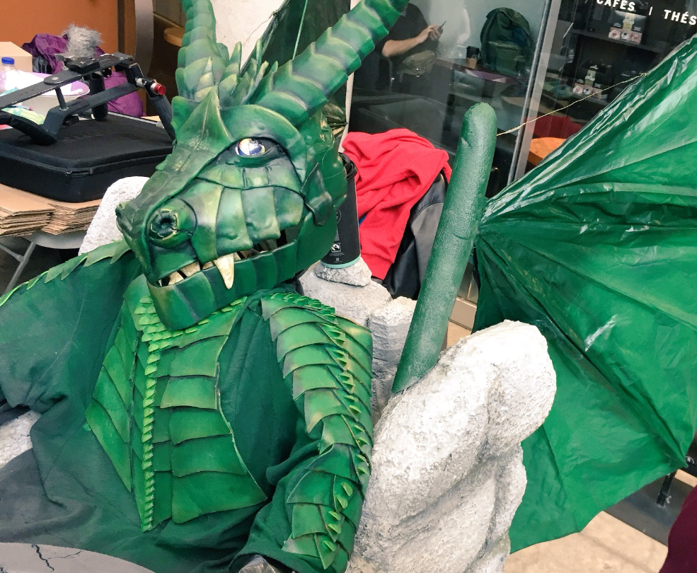 a child in a dragon costume sits in a wheelchair that has been decorated as a castle